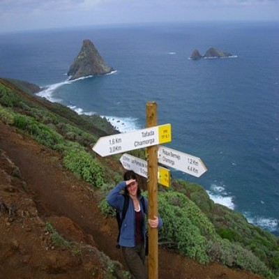 Solo traveller stood by signpost
